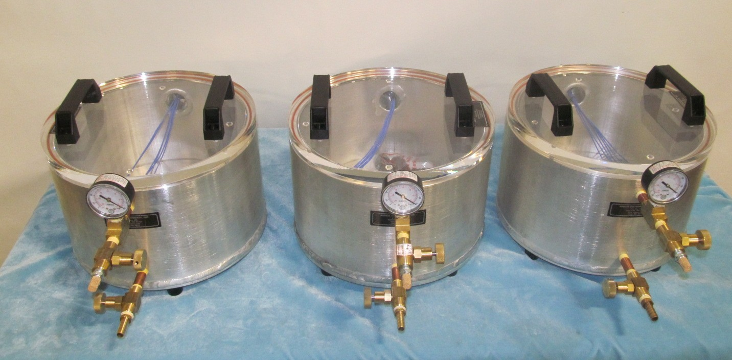 Three aluminum rounds with acrylic lids for dispensing liquids under vacuum.